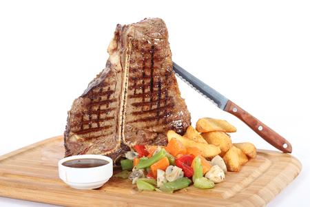 T-bone steak with garniture on wooden plate