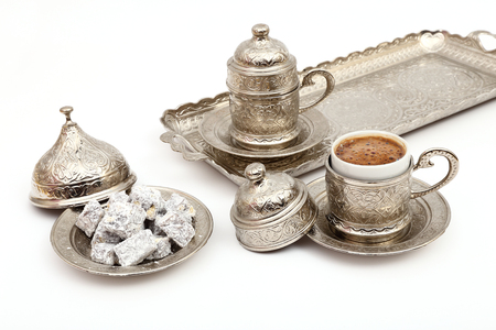 Turkish coffee in traditional silver cup with Turkish delight on isolated white background Imagens