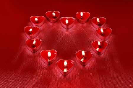 Valentines Day, Heart shaped candles on red background