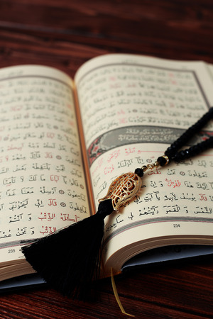 Islamic Holy Book Quran with rosary beads on wooden table background. Kuran the holy book os Muslims. Ramadan concept.