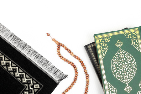 Islamic Holy Book Quran with rosary beads and prayer rug on isolated white background. Kuran the holy book of Muslims. Ramadan concept.