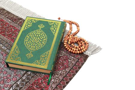 Islamisches Heiliges Buch Koran mit Rosenkranzperlen und Gebetsteppich auf isoliertem weißem Hintergrund. Kuran das heilige Buch der Muslime. Ramadan-Konzept.