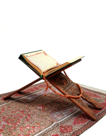 Islamic Holy Book Quran on wood carving rahle with rosary beads and prayer rug on isolated white background. Kuran the holy book of Muslims. Ramadan concept.