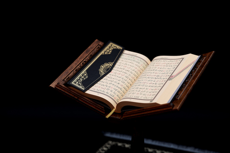 Islamic Holy Book Quran on wood carving rahle with rosary beads and prayer rug on black background. Kuran the holy book of Muslims. Ramadan concept.