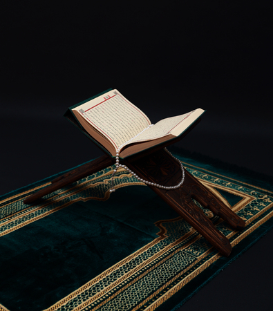 Islamic Holy Book Quran on wood carving rahle with rosary beads and prayer rug on black background. Kuran the holy book of Muslims. Ramadan concept. Stock Photo