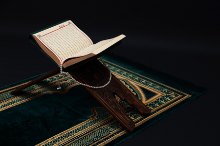 Libro sagrado islámico Corán en rahle tallado en madera con rosario y alfombra de oración sobre fondo negro. Kuran el libro sagrado de los musulmanes. Concepto de Ramadán.