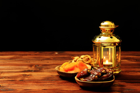 Islamic festival of Ramadan concept. Delicious tropical dates, dried figs, dried apricots on bamboo plates, rosary beads with a lantern on a pine wooden table background. Traditional Middle East culture. Ramadan Kareem. 免版税图像