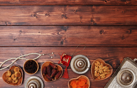 Ramadan concept. Delicious dates, dried figs, dried apricots, walnuts, almonds, raisins on bamboo and silver plates, rosary beads with Islamic holy book Quran on a pine wooden table background.