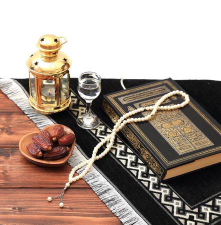 Concept de fête de l'iftar du Ramadan. Livre sacré islamique Coran et chapelet avec de délicieuses dates, figues séchées, abricots séchés sur des assiettes en bambou et lanterne sur fond de table en bois de pin. Kareem Ramadan Banque d'images