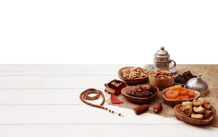 Ramadan iftar party concept. Islamic holy book Quran and rosary beads with delicious dates, dried figs, dried apricots, walnuts, almonds, raisins on bamboo plates on a white wooden table background.