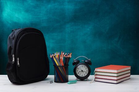 Back to school concept. School bag, pencils, crayons, scissor, notebooks, alarm clock, eraser, markers, watermark ruler, pencil sharpener, magnifying glass in a combine with a cyan background