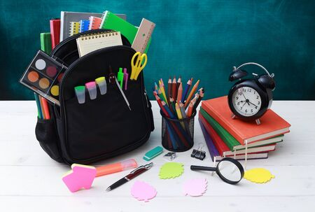 Back to school concept. School bag, pencils, crayons, scissor, notebooks, alarm clock, eraser, markers, watermark ruler, pencil sharpener, magnifying glass in a combine with a cyan background Archivio Fotografico - 132067405