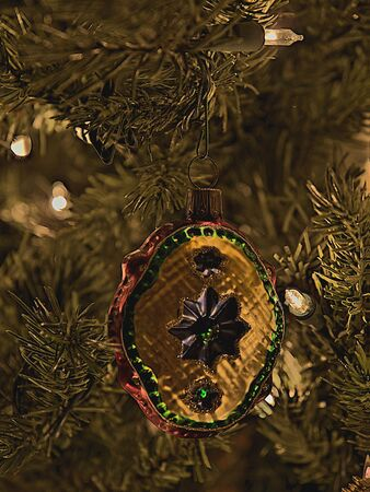Multi-colored glass Christmas tree ornament on a lit tree