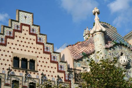 noteworthy: The tops of two famous houses in a modernism style in Barcelona on Gracia boulevard. On the left is casa Amatller by Josep Puig i Cadafalch, on the right is casa Batllo by Antoni Gaudi.