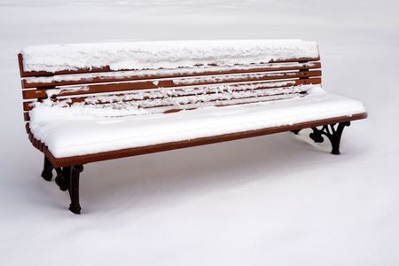 A bench in the park, covered with snow. photo