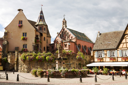 half timbered house: Castle, church and fountain named Saint Leon on the central square of Eguisheim village in France. Eguisheim is a commune in Alsace in north-eastern France. Since 2003 Eguisheim is included into the list of the most beautiful villages of France.