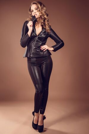 Fashion studio shot of beautiful woman with makeup and hairstyle wearing Leather jackets and pants