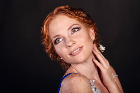 Beautiful woman with red hair and professional make up on black background