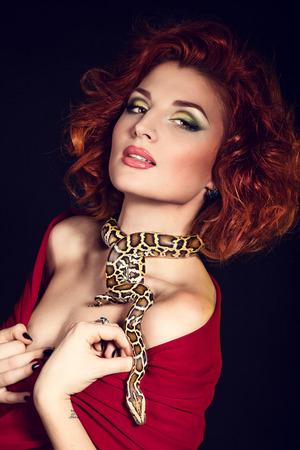 Portrait of Beautiful Woman in studio with dangerous snake. In Greek mythology Medusa was a monster 版權商用圖片