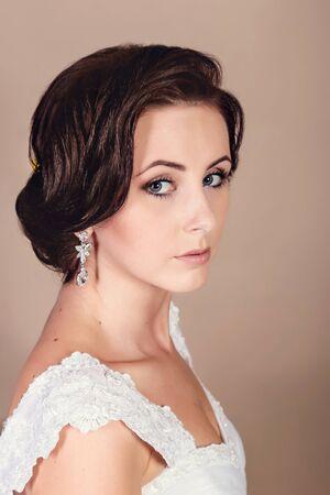 Schöne Braut, die an ihrem Hochzeitstag im Studio auf einem beigen Hintergrund aufwirft. Glückliches Mädchen, das einen Korb mit einem Strauß Tulpen hält