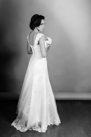 Beautiful bride posing in her wedding day in studio on a beige background. Happy girl holding a basket with a bouquet of tulips