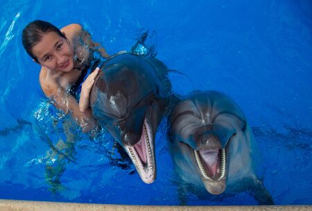 Happy beautiful young girl laughs and swims with dolphins in blue swimming pool on sunny day