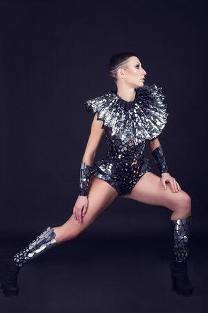 femme de soirée disco vêtue d'un costume unique en argent avec un collier en métal. Parfait pour les événements de club, disco et de mode élégants Banque d'images