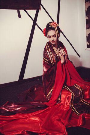 young pretty geisha in kimono with sakura and decoration, with samurai sword