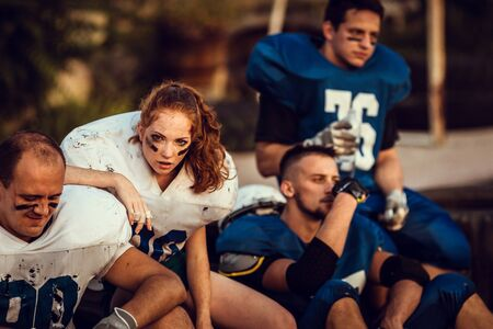 American football woman player in action on the stadium. little girl playing with big men in football on the field at sunset Stock Photo