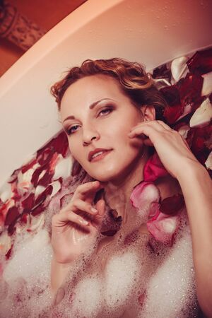 Young woman with red hair take bubble bath with candle. Reklamní fotografie