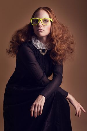 Woman in historical dress with collar in romanticism style. With things from another era - glasses