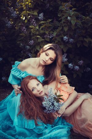 Beautiful women enjoying lilac garden, young women with flowers in green park. cheerful teenagers walking outdoor. soft light style color