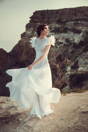 Beautiful bride posing on the coast with angelic dress. Bride in wedding dress stands on a cliff with a beautiful sea view from the top