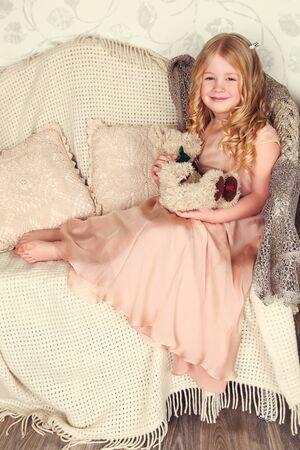 fashion interior photo of beautiful child. Girl in a golden dress Reklamní fotografie