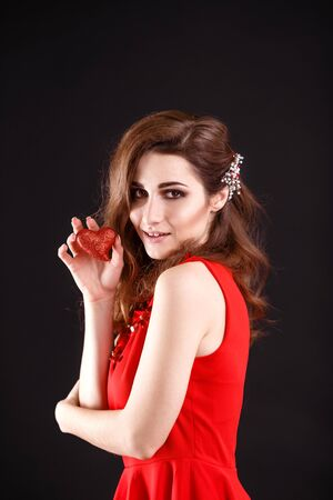 Love and valentines day woman holding heart smiling cute and adorable on black bfckground