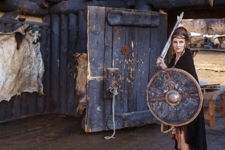 Viking woman with sword and shield in a traditional warrior clothes. Ancient times. Amazon. Fantasy fashion idea.