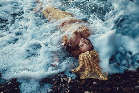 Beautiful fashionable mermaid with red hair and golden scales sitting on a rock by the sea