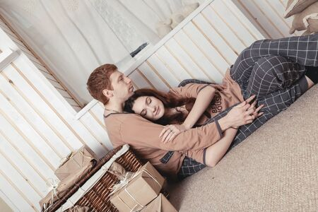 Loving young couple sitting on floor by christmas tree at christmas morning, caressing. happy family couple with a gift on Christmas morning at home