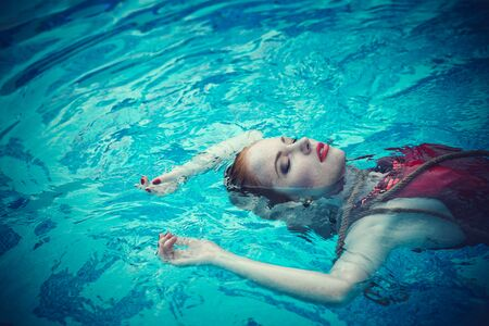 Young woman floating on swimming pool in red dress. Beautiful rich lady who was strangled and thrown off into the water