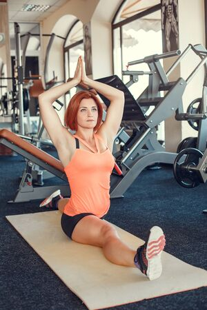 Pretty woman doing stretching exercises at the gym. Young attractive woman does splits crossfit stretching in gym club