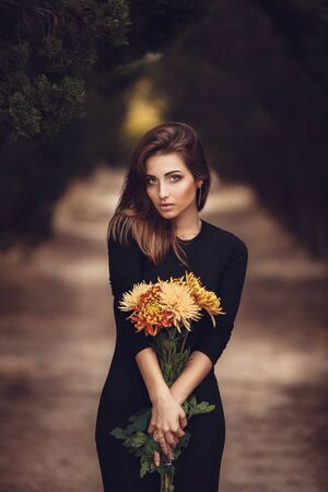 Beautiful young smiling brunette woman with flowers in autumn park