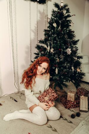 attractive young woman in a winter fashion shot wearing a white woolen sweater and a knitted socks. New year and Christmas.