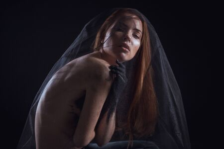 Beautiful model with red hair posing behind a black fabric and a veil in a studio Standard-Bild