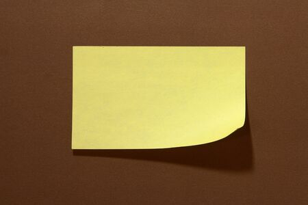 Single wide Post-it on brown background Stock Photo - 16431605