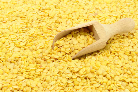 Yellow Lentils and wooden spoon closeup