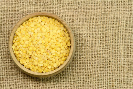 Yellow Lentils, wooden cup on sackcloth