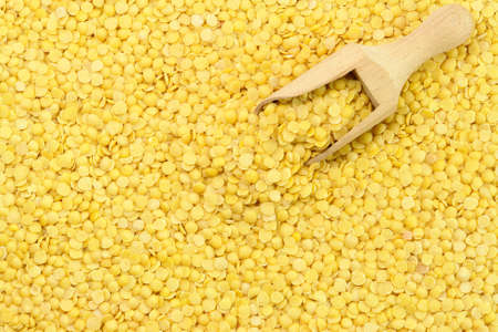 Yellow Lentils and wooden spoon from top Stock Photo