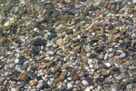 small sea pebbles in the water. Smooth stones Zdjęcie Seryjne
