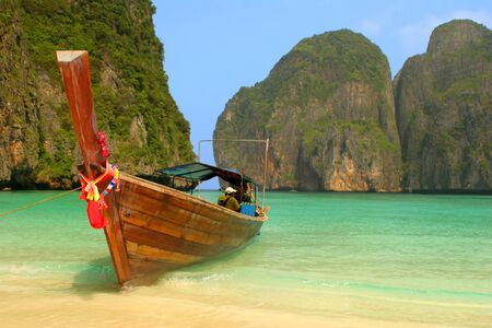 Colourfully decorated boat at Maya Bay: an idyllic beach on Phi Phi Ley - the scene of the film  Stock Photo