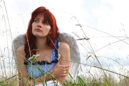 The beautiful girl an angel sitting in a grass